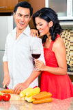 Asian couple preparing food in domestic kitchen Royalty Free Stock Images