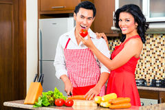 Asian couple preparing food in domestic kitchen Stock Photos