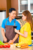 Asian couple preparing food in domestic kitchen Royalty Free Stock Photo