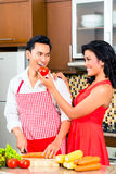Asian couple preparing food in domestic kitchen Royalty Free Stock Image