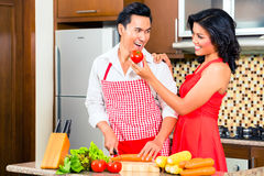 Asian couple preparing food in domestic kitchen. Asian couple cooking and cutting vegetables in domestic kitchen, drinking red wine Royalty Free Stock Photography