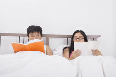 Asian couple reading books while looking at each other in bed Royalty Free Stock Photography