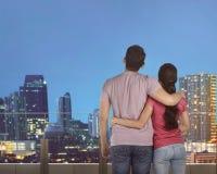 Asian couple relaxing on terrace enjoying modern city landscape Royalty Free Stock Image