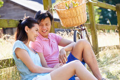 Asian Couple Resting By Fence With Old Fashioned Cycle Royalty Free Stock Images