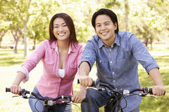 Asian couple riding bikes in park Royalty Free Stock Images