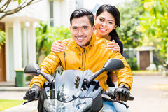 Asian couple riding motorcycle Royalty Free Stock Image