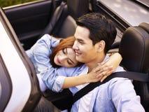 Asian couple riding in a sports car Stock Photos
