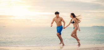 Asian couple run togather on the beach Stock Images