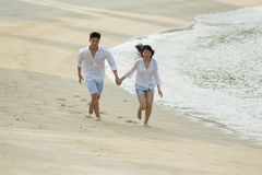 Asian couple running the beach. Royalty Free Stock Photos