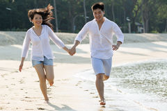 Asian couple running the beach. Royalty Free Stock Photo