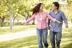 Asian couple running through in park Royalty Free Stock Image