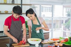 Asian couple`s in apron, make salads together.  man are preparing to cut vegetables with knives. Woman mix salad dressing stock image