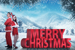 Asian couple in santa claus costume posing on merry christmas text Royalty Free Stock Photos