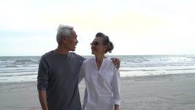 Asian couple senior elder retire resting relax walking at sunset beach honeymoon