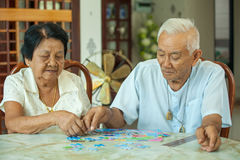 Asian couple senior playing with a jigsaw puzzle. At home stock images