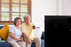Asian couple senior sitting on sofa and use remote control to change channel and watching tv in living room at home.panning from. Blur foreground television royalty free stock photography