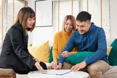 Asian couple sign home contract and handshake with realtor at living room in new home.buying new house real estate.  royalty free stock image