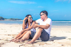 Asian couple sitting on the beach of tropical Bali island, Indonesia. Royalty Free Stock Images