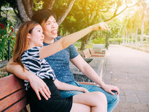 Asian couple sitting on the bench in the park together Royalty Free Stock Photo