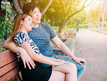 Asian couple sitting on the bench in the park together Stock Photography
