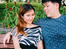 Asian couple sitting on the bench in the park together Stock Images