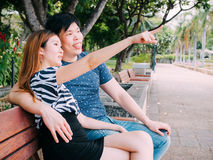 Asian couple sitting on the bench in the park together Stock Photos