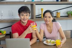 Asian couple, sitting at the dining table. Both of them are smiling happily. woman send the glass of orange juice to the male. And stock photography