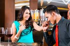Asian couple sitting in restaurant. Happy Asian couple sitting in restaurant Stock Image