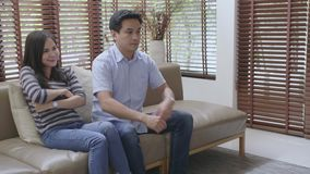 Asian couple fighting over the remote control in front of TV stock video