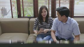Asian couple fighting over the remote control in front of TV stock footage