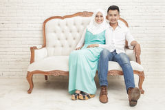 Asian couple sitting on sofa while looking at camera Stock Images