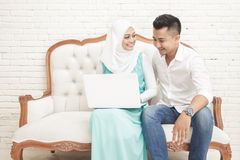 Asian couple sitting on sofa while using laptop together Stock Photo
