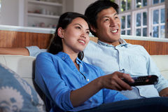 Asian Couple Sitting On Sofa Watching TV Together. Holding Remote Control Stock Photos