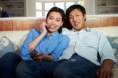 Asian Couple Sitting On Sofa Watching TV Together Royalty Free Stock Images