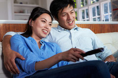 Asian Couple Sitting On Sofa Watching TV Together. Relaxing At Home Royalty Free Stock Photos