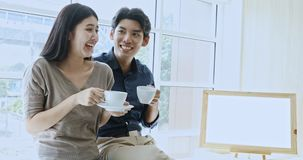 Couple drinking coffee. Asian couple sitting together near window, they drinking coffee and talking, concept for time sharing and relaxing in family stock video