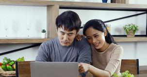 Asian couple sitting and using laptop together. stock video footage