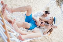 Asian couple sleep on swing net and play an ukulele and sing a s. Ong togather in resort in Phuket beach, Thailand, Travel, valentine, love and summer concept Stock Photo