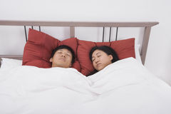 Asian couple sleeping in bed Stock Image