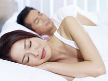 Asian couple sleeping in bed Royalty Free Stock Image