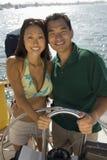 Asian Couple Steering A Sailboat Stock Photos