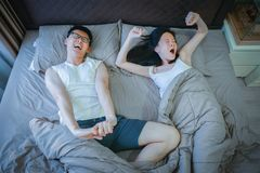 Asian couple stretching on bed in bedroom royalty free stock photography