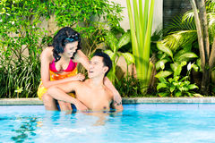 Asian couple swimming in resort pool Stock Photography