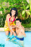 Asian couple swimming in resort pool Royalty Free Stock Images