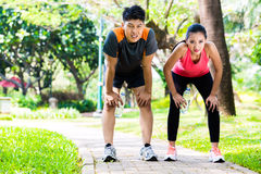 Asian couple take breathless break from running. Asian Chinese men and women are out of breath after jogging in city park for sport fitness Royalty Free Stock Images