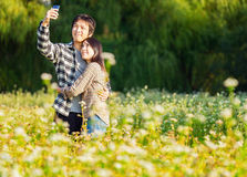 Asian couple take photo. By mobile phone Stock Photos