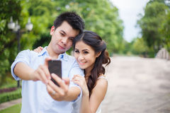 Asian couple take photo by mobile phone in a garden - selfie Royalty Free Stock Photography