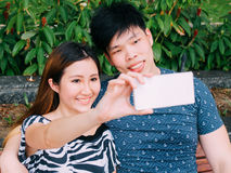 Asian couple taking a selfie photo in outdoor park scene Stock Photo