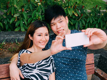Asian couple taking a selfie photo in outdoor park scene - love Stock Image