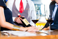 Asian couple tasting red wine in bar Royalty Free Stock Photos